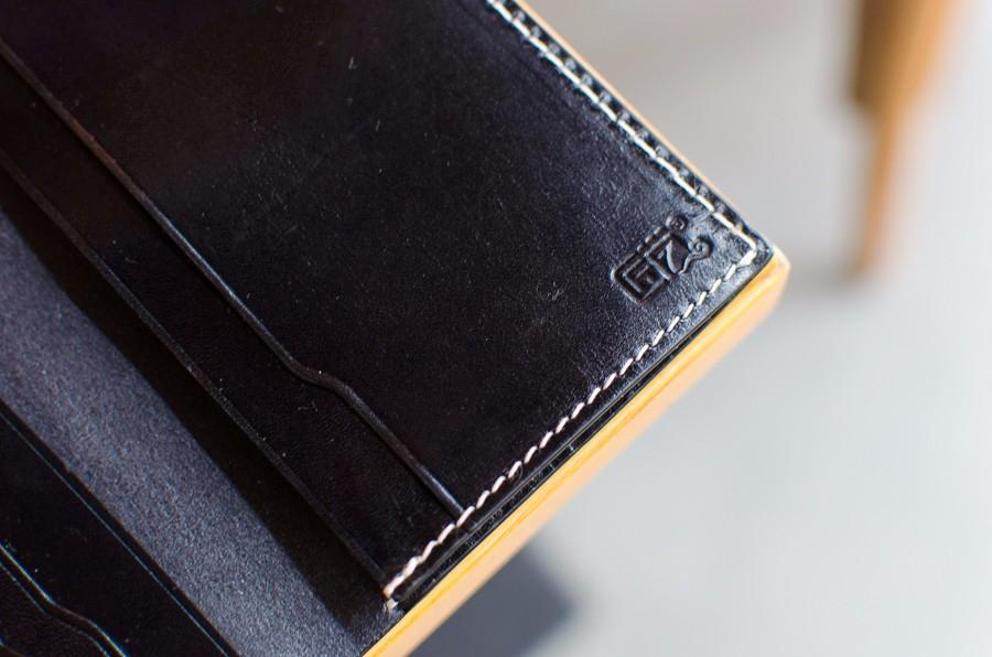 白色的缝线在深色的包身上比较凸显效果,真皮与红木结合处的十字交叉